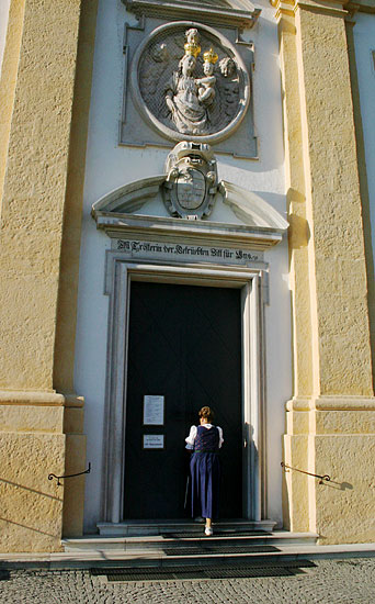 Lady in Dirndl dress entering a church in Salzburg